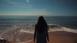 Back view of a beautiful girl with long brown hair walking barefoot into the sea