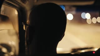 Back view of bald man with earrings inside the car. Car riding throug the empty road late at night.