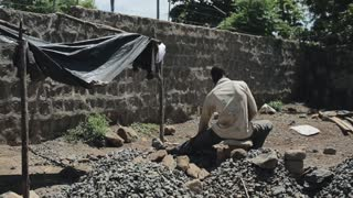 Back view of man from Africa works at construction site. Guy is sitting on the quarry
