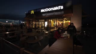 Barcelona, Spain - April 27, 2018: A young couple eating at McDonald s summer tables late in the evening. McDonalds fast food restaurant on the highway. A stop for resting and eating during a road