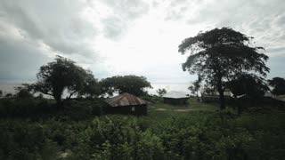 Beautiful landscape of a poor village in Africa. Small houses stand on the sea.