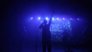 Blue light. A man with a lifted up hand singing on stage. A music group at a concert. Blurred vision