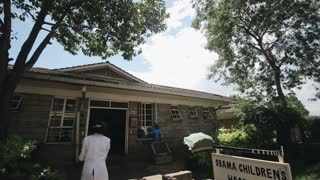 Doctors in white coats come into a hospital in a small city in Africa. People go to work.