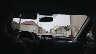 Driving a car along the street of a nice town. Two-storey houses on both sides of the road. A male driver and a female passenger. View from the rear seat