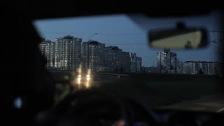 Driving in the city in the evening. Tall apartment buildings on one side of the road