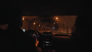 Family couple travels by car in the evening. The car goes through a tunnel and drives onto a winding mountain road. Back view