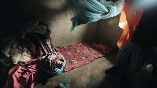 Inside a poor little house in Africa. A lot of clothes, linen lies on the concrete floor.