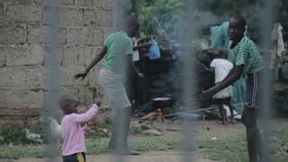 KENYA, KISUMU, 15. 05. 2018. View through fence. African children walking in house yard. Boys doing gymnastic exercises.