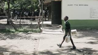 KENYA, KISUMU - MAY 20, 2017: African children in uniform is walking near school with plastic bottles.