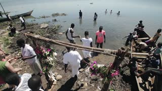 KENYA, KISUMU - MAY 20, 2017: Baptizing of African people in the lake. Men and women come into the water.