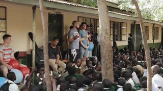 KENYA, KISUMU - MAY 20, 2017: Caucasian men standing and talking in African school to group of children.