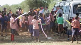 KENYA, KISUMU - MAY 20, 2017: Caucasian volunteers come to african school. Children playing with balloons.