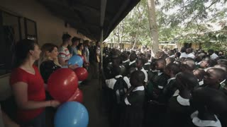 KENYA, KISUMU - MAY 20, 2017: Caucasian volunteers dancing with balloons, with big group of African children.