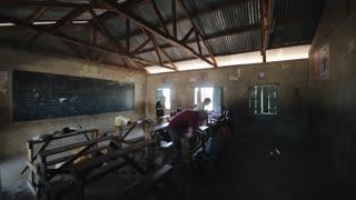 KENYA, KISUMU - MAY 20, 2017: Caucasian volunteers in small African school, helping children in classes.