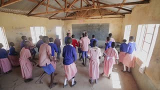 KENYA, KISUMU - MAY 20, 2017: Caucasian women dancing with African children in small local school.