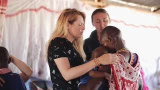 KENYA, KISUMU - MAY 20, 2017: Caucasian women pray for African family, young mother with her son.