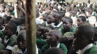 KENYA, KISUMU - MAY 20, 2017: Close-up view of African boys and girls sitting in a big crowd of pupils outside school.