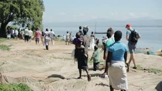 KENYA, KISUMU - MAY 20, 2017: Group of african and caucasian people with children walking on the shore of the sea.