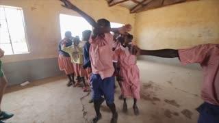 KENYA, KISUMU - MAY 20, 2017: Happy african children repeating dancing movements after Caucasian men.