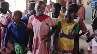 KENYA, KISUMU - MAY 20, 2017: Happy african children repeating dancing movements after Caucasian women.