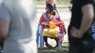 KENYA, KISUMU - MAY 20, 2017: Old African woman from local maasai tribe sitting on chair and hold balloon.