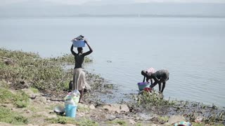 KENYA, KISUMU - MAY 20, 2017: Woman and her daughter wash dishes in lake, girl carry basin with clothes on head.