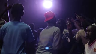 KENYA, KISUMU - MAY 20, 2017:African boys and girls, teenagers dancing together in dark room with bright light.