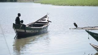 KENYA, KISUMU - MAY 20, 2017:Beautiful landscape of African man sitting in the boat, swimming in sea alone.