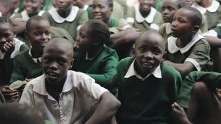 KENYA, KISUMU - MAY 20, 2017:group of African children in green uniform sitting on ground, smiling, talking.