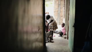 KISUMU,KENYA - MAY 15, 2018: African children are sitting near the house. A little girl combs, plaits her sister's hair.