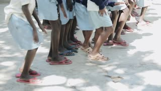 KISUMU,KENYA - MAY 15, 2018: Close-up view of group of african children stomp their feet and clap hands, dancing.
