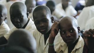 KISUMU,KENYA - MAY 15, 2018: Close-up view of three african boys in uniform sitting in classroom in school