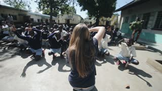 KISUMU,KENYA - MAY 15, 2018: Crowd dancing outside in Africa. Caucasian woman showing motions african children