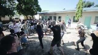 KISUMU,KENYA - MAY 15, 2018: Crowd dancing outside in summer. Men, women and kids having fun together in Africa.