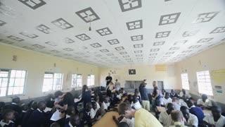 KISUMU,KENYA - MAY 15, 2018: Group of african children and caucasian volunteers have activities in school together