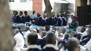 KISUMU,KENYA - MAY 15, 2018: Group of african children and teenagers in uniform sitting on school backyard and looking