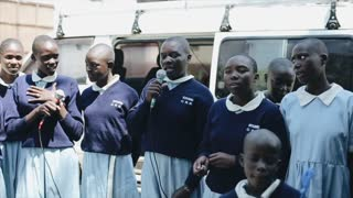 KISUMU,KENYA - MAY 15, 2018: Group of african children, girls in uniform singing song together in microphone in summer.