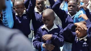 KISUMU,KENYA - MAY 15, 2018: Group of african children in uniform dancing together. Boys and girls having fun together