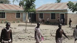KISUMU,KENYA - MAY 15, 2018: Group of African children in uniform playing football in the school yard. Poor village in Africa.