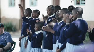 KISUMU,KENYA - MAY 15, 2018: Group of african children in uniform standing together outside and clapping their hands