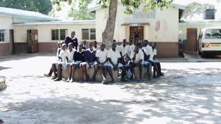 KISUMU,KENYA - MAY 15, 2018: Group of african children sitting on bench. Boys and girls spending time near the school.