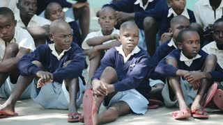 KISUMU,KENYA - MAY 15, 2018: Group of african children sitting on ground. Boys and girls in uniform spend time outside.