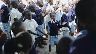KISUMU,KENYA - MAY 15, 2018: Group of african kids clap their hands and singing song. Boys and girls having fun together.