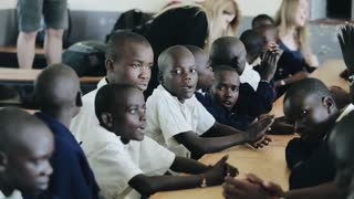 KISUMU,KENYA - MAY 15, 2018: Group of bald african children sitting. Boys and girls in uniform sing song and clap hands.