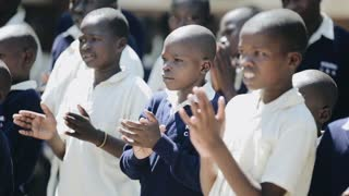 KISUMU,KENYA - MAY 15, 2018: Group of bold african kids in uniform standing near the school and clapping hands