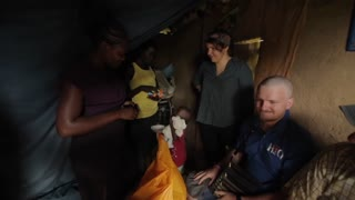 KISUMU,KENYA - MAY 15, 2018: Group of Caucasian volunteers come to house of poor African family with presents to help.