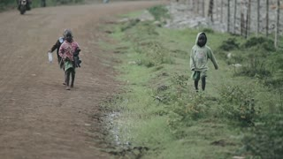 KISUMU,KENYA - MAY 15, 2018: Three African children are running along the road. Girl and boys playing outside.
