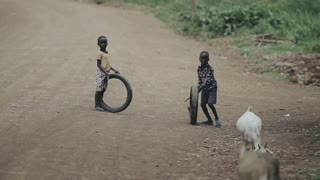 KISUMU,KENYA - MAY 15, 2018: Two african boys playing with tires on the road. Kids having fun together.