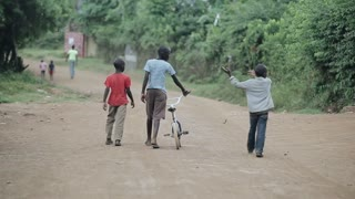 KISUMU,KENYA - MAY 17, 2018: Back view of boys walking through the road in Africa. Male with bicycle walking in forest.