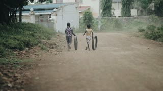 KISUMU,KENYA - MAY 17, 2018: Back view of two african boys running through road and playing with car tire in village.